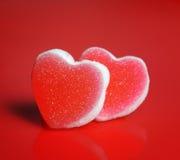 Sockerhjärtor på röd bakgrund. Valentinbegrepp arkivbild