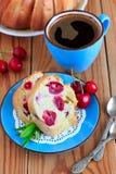 Sockerkaka med körsbär på den blåa plattan Royaltyfri Fotografi