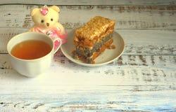 Sockerkaka med vallmofrön på en platta, en kopp te och en nallebjörn som ligger på en trätabell royaltyfri fotografi