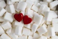 Sockerkuber med bakgrund för två röd hjärtor close upp Top beskådar Arkivfoto