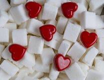 Sockerkuber med bakgrund för två röd hjärtor close upp Top beskådar Arkivbild