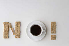 Sockerkuber och kopp kaffe som är ordnade som ordet INTE på vit bakgrund Banta det unhealty söta böjelsebegreppet Arkivfoto