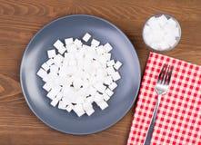 Sockerkuber på en platta och i ett exponeringsglas För mycket socker i matbegrepp fotografering för bildbyråer