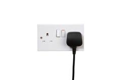 Socket on. British socket and black plug. Socket turned on. isolated on white stock images
