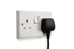 Socket on. British socket and black plug. Socket turned on royalty free stock image
