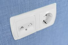 Socket on a blue wall, a multifunction outlet with an internet connection and european-style outlets stock photo