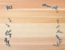 Socket head bolts as border on wood Stock Photos