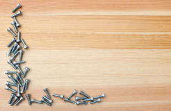Socket head screws as L-shape border on woodgrain background Stock Photo