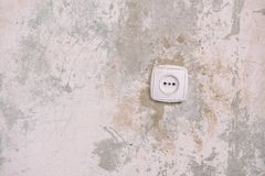 Socket on the nosing wall. Wall without wallpaper. Old wall. Repair in the apartment. Scratched wall in the apartment. Socket royalty free stock images