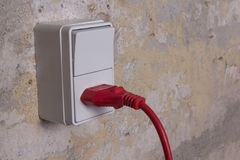 Socket with red wire on grungy wall Royalty Free Stock Image