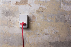 Socket with red wire on grungy wall Stock Image
