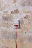 Socket with red wire on grungy wall Stock Images