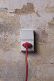 Socket with red wire on grungy wall Stock Photo