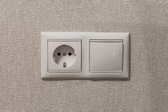 Socket and switch on beige wall close-up stock photo