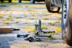 Socket wheel wrench and jack lying on ground Stock Images