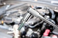 Socket wrench. A shiny chrome socket wrench in front of a car engine before for servicing and repair royalty free stock photo