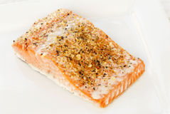 Sockeye Salmon. Baked Alaskan Sockeye salmon covered with lemon pepper seasoning blend. Served on a white plate with an antique linen tablecloth in the Royalty Free Stock Image