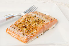 Sockeye Salmon. Baked Alaskan sockeye salmon with lemon pepper herbs garnished on top. Served on a white plate with an antique linen tablecloth in background Royalty Free Stock Images