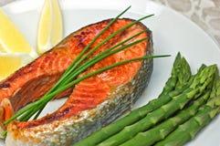 Sockeye salmon steak dinner. Fresh grilled sockeye salmon steak dinner with asparagus and lemon wedges Royalty Free Stock Image