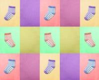 Sockor för barn ovanför sikt Mång--färgade randiga sockor på för lilor, violetta och gröna bakgrunder för rosa färger, för senap, Arkivbilder
