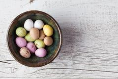 Sockra bestrukna spräckliga easter ägg i keramisk bunke på vit Royaltyfria Bilder