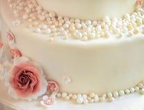 Sockra rosor med pärlor på kakacloseupen arkivbilder