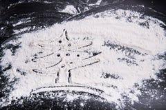 Sockra upp pulverjulgranen på en svart träbakgrund, slut, kopieringsutrymme Mjöl för prydnader för julpulverbakgrund Royaltyfri Bild