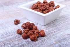 Sockrade hasselnötter i en vit bunke på en träbakgrund Hasselnötter i sockerglasyr Selektivt fokusera Arkivfoton