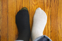 Socks. Men in two color socks on the wood floor. Confusing Royalty Free Stock Image