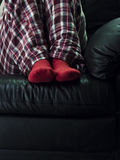 Socks. Feet relaxing on couch in red socks Stock Photography