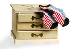 Socks as the American flag on dresser. Children's dresser with an open top drawer from which protrude socks as the American flag isolated on white background Royalty Free Stock Photo