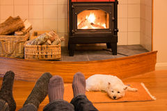 Socks and feet of a couple relaxing by fire with west highland t Stock Photo