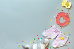 Socks, soother, teether and sleeping cat toy over grey background. Baby girl accessories concept: socks, soother, teether and sleeping cat toy, over grey royalty free stock images