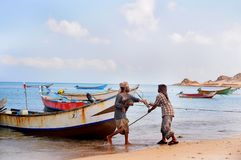 Socotra, Yemen, March 9, 2015 Simple rural fishermen returning from fishing to drag the boat out of the water on the shores of an stock images