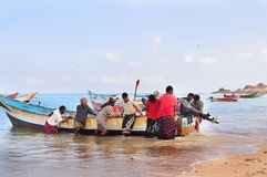 Socotra, Yemen, March 9, 2015 Simple rural fishermen returning from fishing to drag the boat out of the water on the shores of an stock photography