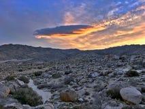 Soczewkowate chmury tworzą nad jałowym pustynia krajobrazem podczas kolorowego zmierzchu Obrazy Stock