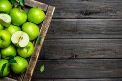 Soczyści zieleni jabłka i Apple plasterki w drewnianym pudełku fotografia royalty free