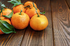 Soczyści dojrzali tangerines z liśćmi na drewnianych tła zbliżenia zdrowie organicznie v Fotografia Royalty Free
