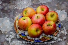 Soczyści jabłka na kwiecistej tło szarości Zdjęcie Stock