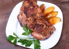 Soczyści wieprzowiny szyi kotleciki piec na grillu z grulami na białym talerzu zdjęcia royalty free