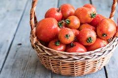Soczyści dojrzali organicznie pomidory w koszu na drewnianym tle Obraz Royalty Free