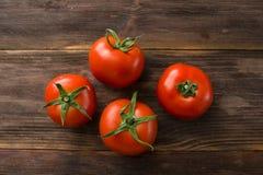 Soczyści dojrzali pomidory na drewnianym stole Zdjęcia Stock