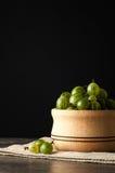 Soczyste dojrzałe jagody agrest w małym drewnianym garnku na czerni ukazują się Agrestowy żniwo Fotografia Stock