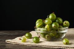 Soczyste dojrzałe jagody agrest w małym szklanym talerzu na czerni ukazują się Agrestowy żniwo Obrazy Stock