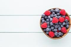 Soczyste i świeże czarne jagody z zielenią wybijają monety na nieociosanym błękita stole Zdjęcia Royalty Free