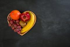 Soczyste owoc ustawiać w drewnianym sercu kształtowali talerza Zdjęcia Stock