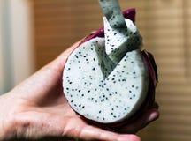 Soczystego smoka owocowy lying on the beach w ręki przecinania kawałka owocowym trójgraniastym zakończeniu obraz royalty free