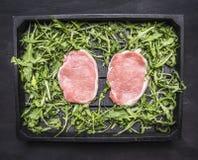 Soczysty świeży surowy wieprzowina stek z arugula na drewnianej tacy tła odgórnego widoku drewnianym nieociosanym zakończeniu up obrazy royalty free