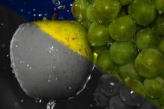 Soczysty żółty jabłko i zieleni winogrono z wod kropel połówką czarny i biały Fotografia Royalty Free