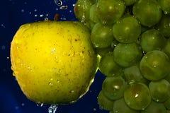 Soczysty żółty jabłko i zieleni winogrono z wod kroplami na błękitnym tle Obraz Stock